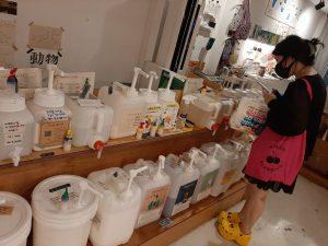 אישה קוריאנית בוחנת מיכלים למילוי (Re-fill) שמפו רב פעמי בחנות Zero Waste במרכז סיאול